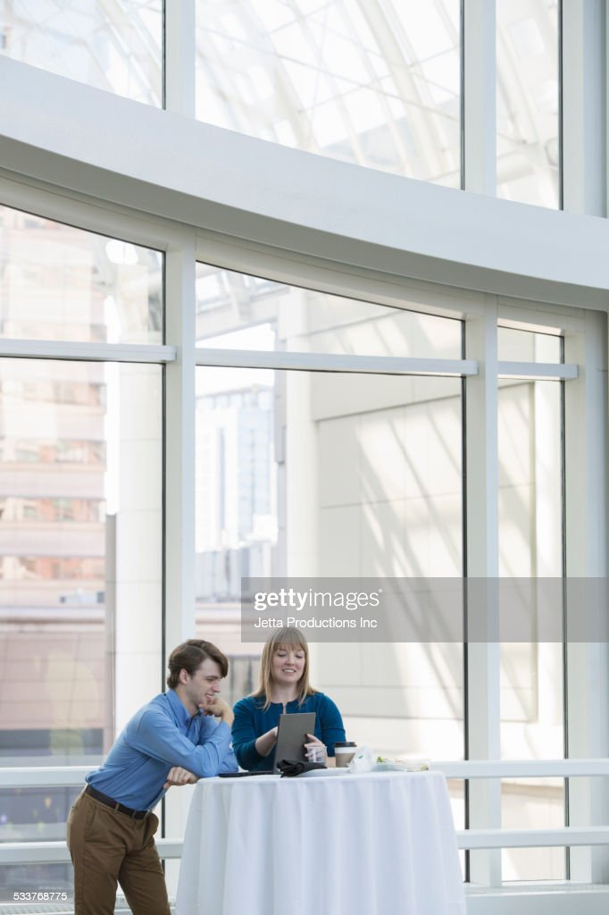 Caucasian business people using digital tablet at table : Foto stock