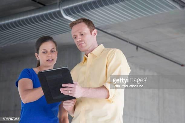 Caucasian business people using digital tablet