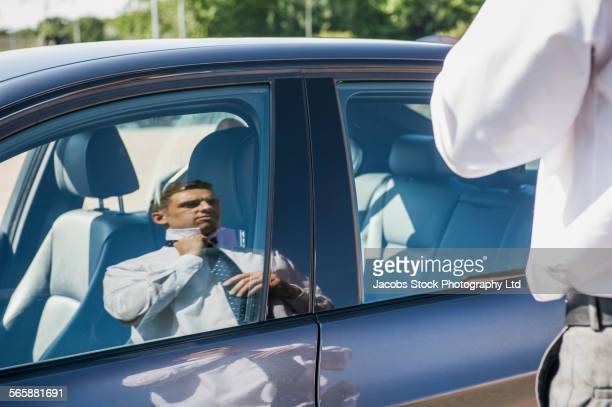 Caucasian businessman adjusting tie in car window