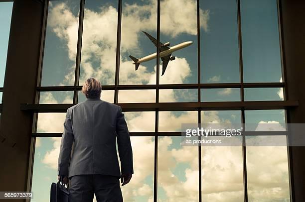 Caucasian businessman admiring airplane from airport windows