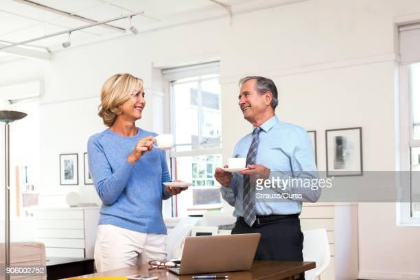 Caucasian businessman and businesswoman drinking coffee