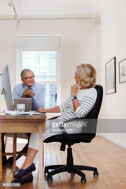 Caucasian businessman and businesswoman talking at table