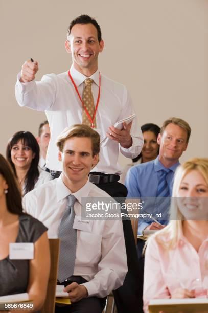 Caucasian businessman asking questions in presentation