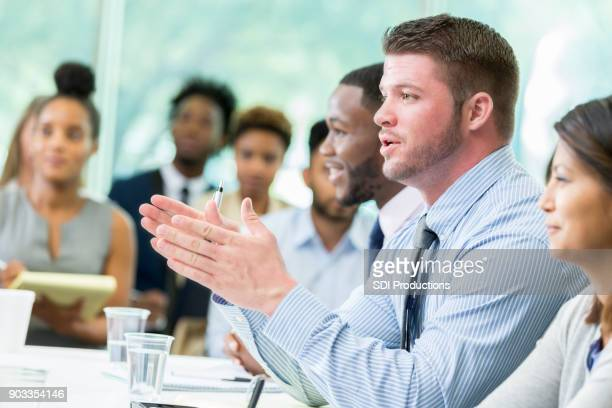 Caucasian businessman asks question during continuing education class