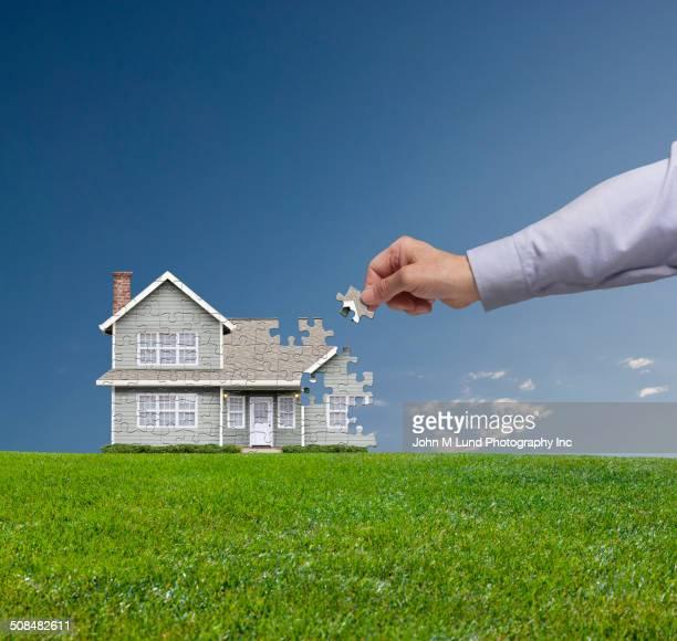Caucasian businessman building house with puzzle pieces