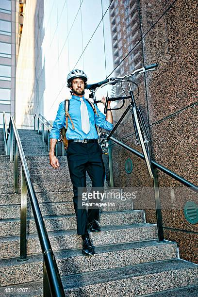 Caucasian businessman carrying bicycle down urban stairs