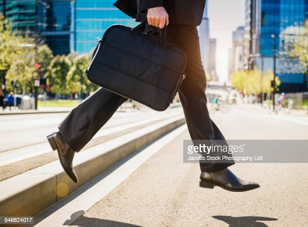 caucasian businessman carrying briefcase across city street - curb stock pictures, royalty-free photos & images