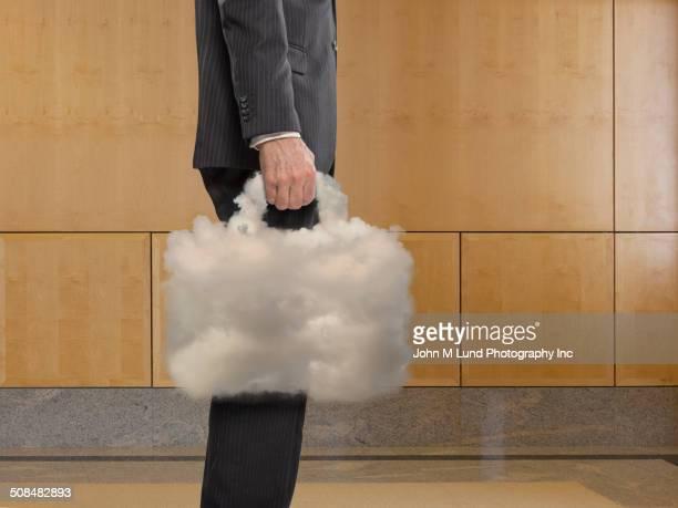 Caucasian businessman carrying cloud briefcase