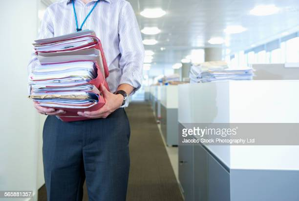 Caucasian businessman carrying paperwork in office