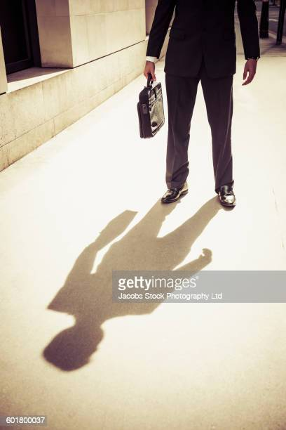 Caucasian businessman casting shadow on sidewalk