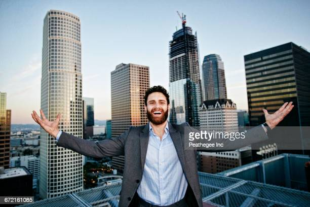 Caucasian businessman celebrating on urban rooftop