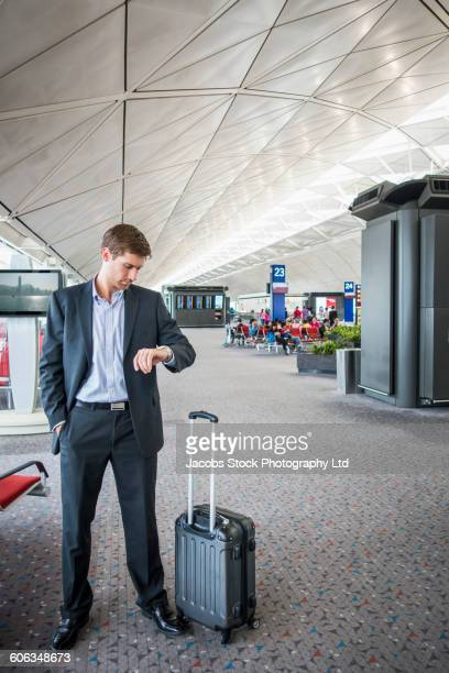 caucasian businessman checking watch in airport - impatient stock pictures, royalty-free photos & images
