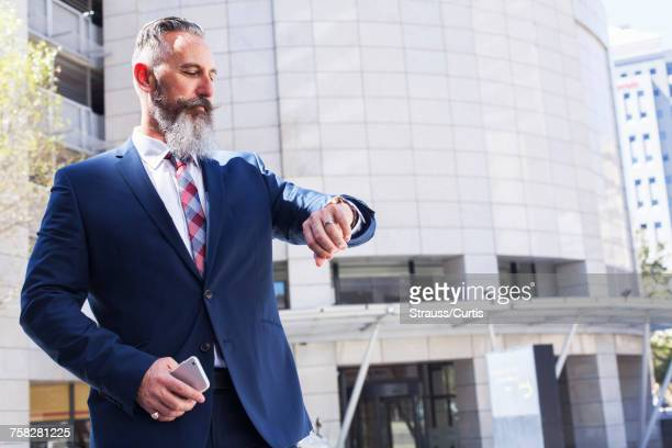 Caucasian businessman checking wristwatch outdoors