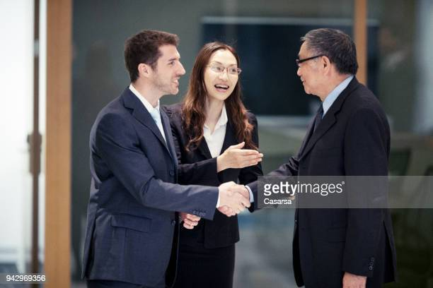 Caucasian Businessman closing a deal in Hong Kong with his Asian colleagues