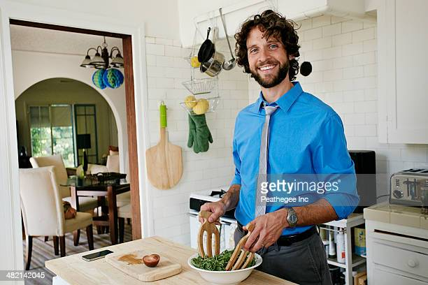 Caucasian businessman cooking in kitchen