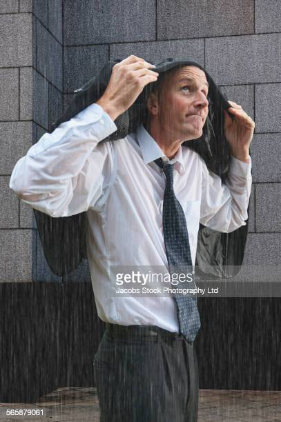 Caucasian businessman covering head with suit jacket in rain storm