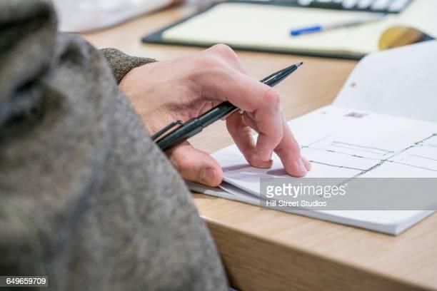 Caucasian businessman drawing diagram in office meeting