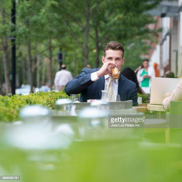 Caucasian businessman drinking at cafe outdoors