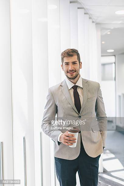 Caucasian businessman drinking coffee in office corridor