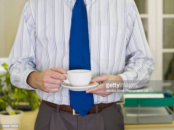 caucasian businessman drinking cup of coffee in office - spalding england stock photos and pictures