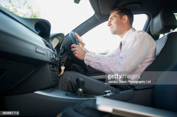 Caucasian businessman driving car