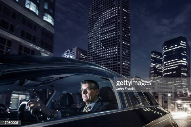 Caucasian businessman driving on city street