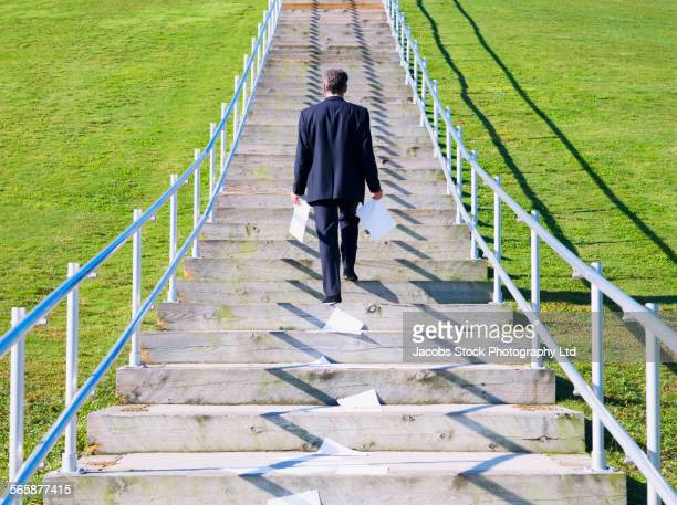Caucasian businessman dropping trail of paperwork on outdoor staircase