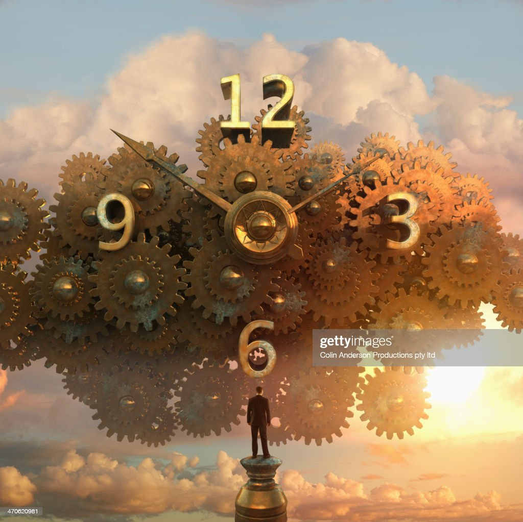 Caucasian businessman examining clock in sky : Stock Photo