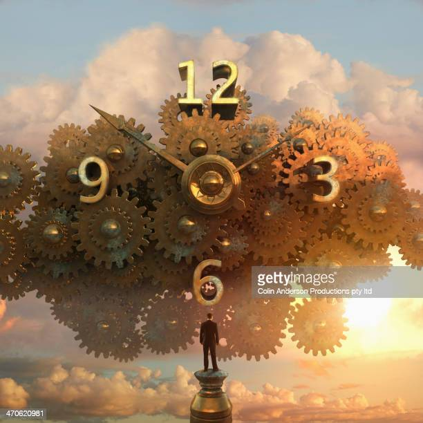 Caucasian businessman examining clock in sky