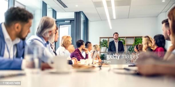 homme d'affaires caucasien donnant un discours aux personnes s'asseyant à une table de conférence - réunion photos et images de collection