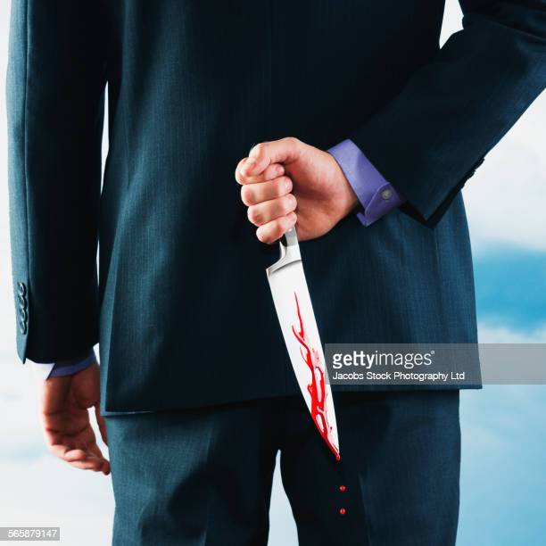Caucasian businessman hiding bloody dagger behind back