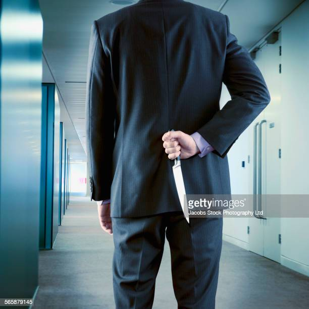 Caucasian businessman hiding dagger behind back