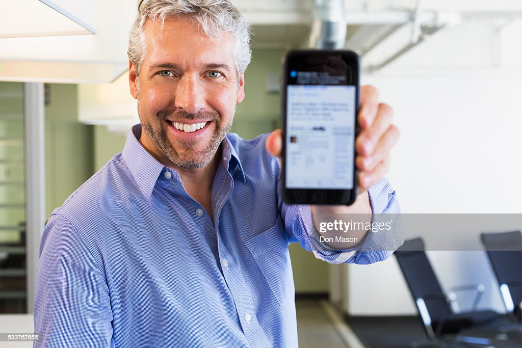 Caucasian businessman holding cell phone in office : Stock-Foto