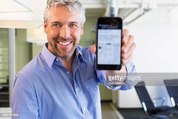 caucasian businessman holding cell phone in office - mostrare foto e immagini stock