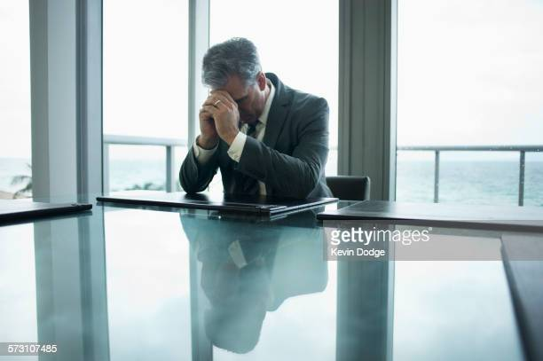 Caucasian businessman holding head in hands at conference table