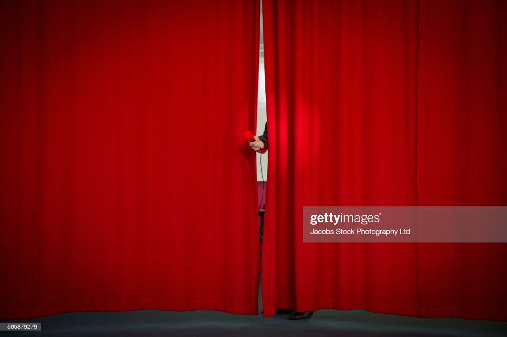 Caucasian businessman holding microphone from behind curtain : Stock Photo