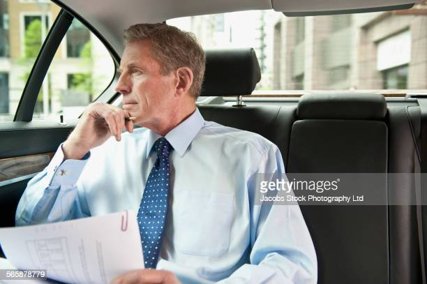 Caucasian businessman holding paperwork in back seat of car