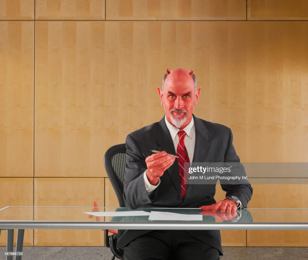 Caucasian businessman in devil costume offering pen to sign contract : Stock Photo