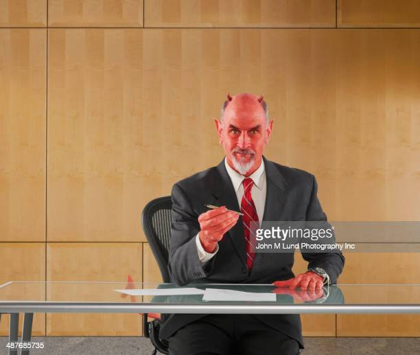 caucasian businessman in devil costume offering pen to sign contract - devil costume stockfoto's en -beelden