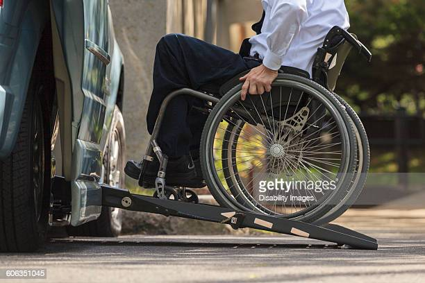 caucasian businessman in wheelchair entering van - assistive technology stock photos and pictures