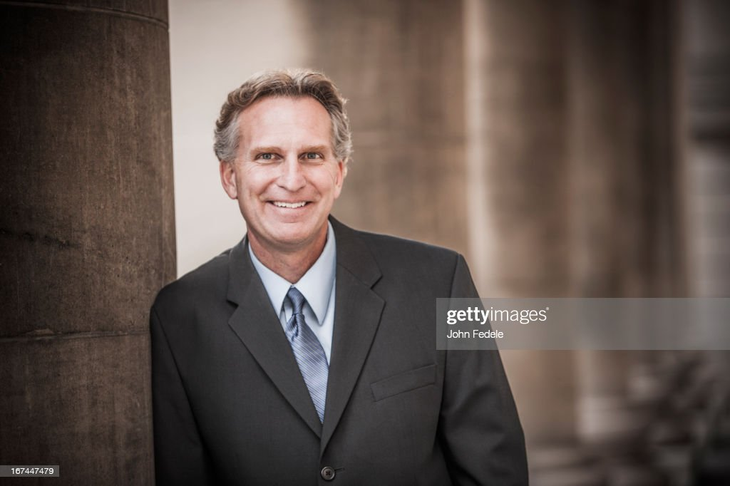 Caucasian businessman leaning on pillar : Stock Photo
