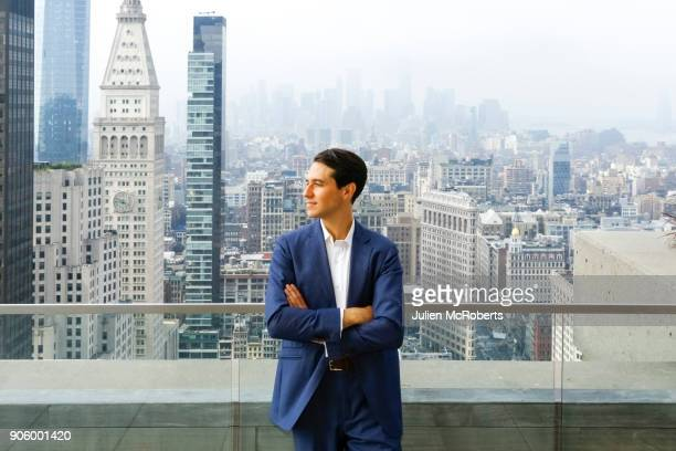 caucasian businessman leaning on urban rooftop - 屋根 ストックフォトと画像