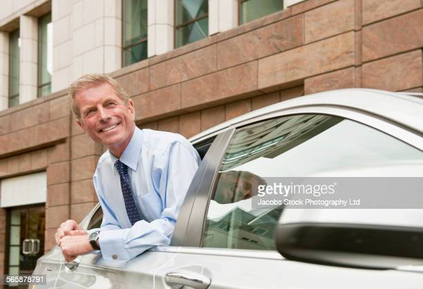 Caucasian businessman leaning out car window