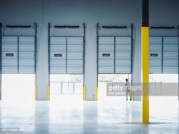 caucasian businessman lifting loading dock door - loading dock stock pictures, royalty-free photos & images