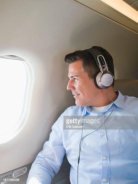 Caucasian businessman listening to headphones on airplane