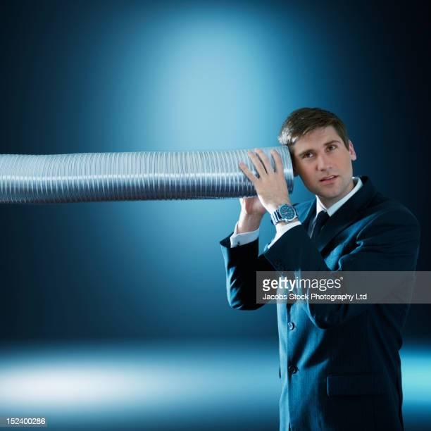 Caucasian businessman listening to tube