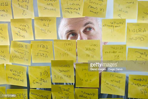 Caucasian businessman looking at adhesive notes on wall