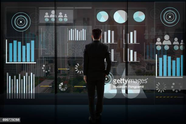Caucasian businessman looking at graphs on monitors