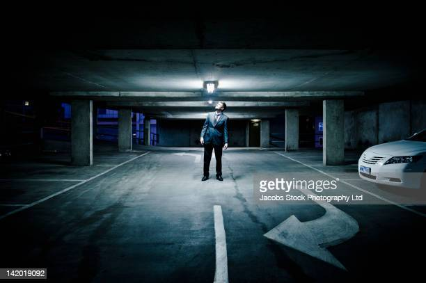 Caucasian businessman looking at light in parking garage
