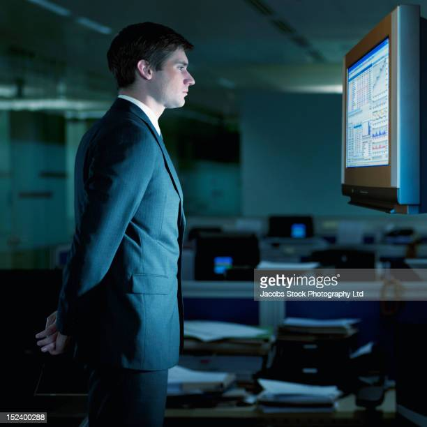 Caucasian businessman looking at monitor in office